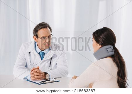 doctor sitting and talking with patient in neck brace