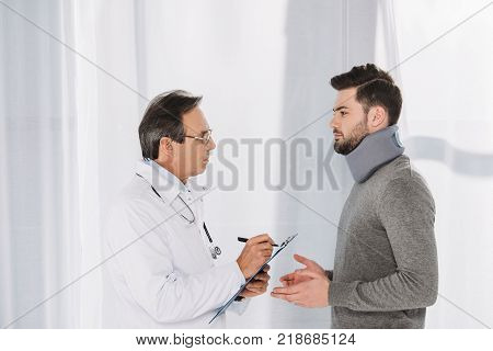 doctor writing down to clipboard after patient in neck brace
