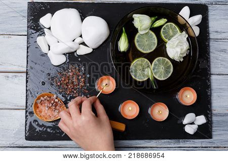 The hand of a young European woman who lights a small aroma candle with a match, next to a set for aroma procedures, a variety of pebbles, slices of lemon and buds of white flowers. View from above.