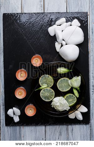 On a dark stone board there is a set for aroma spa procedures from a different-shaped white pebble, small aroma of candles and a deep dark bowl with water, slices of lemon and buds of beautiful white flowers. View from above.
