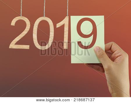 concept of starting a new year of 2019 on twilight sky backgroundhand of a businessman holding a paper note with eight numbers.