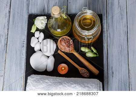 Aroma oils, aroma candles and various pebbles for spa and aroma treatments on a dark stone board. View from above.