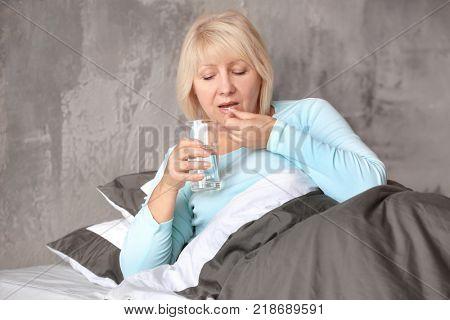 Mature woman taking medicine at home