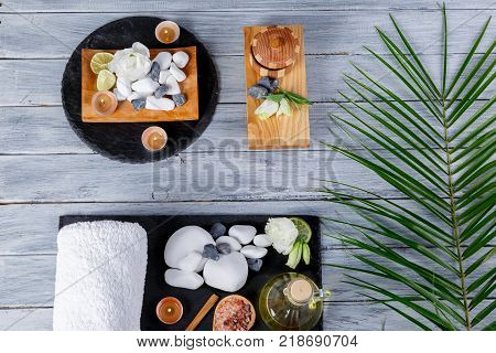 Various pebbles, aroma oils, burning candles and towels for spa and aroma treatments, on various boards on a wooden surface. View from above.