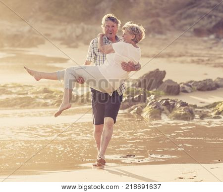 lovely senior mature romantic couple on their 60s or 70s retired walking happy and relaxed on beach sea shore in romantic aging together and retirement husband and wife lifestyle concept