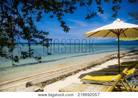 beautiful marine landscape view of amazing tropical paradise beach with white sand and amazing turquoise color sea water and yellow sun beds with umbrella in Summer travel destination holiday concept