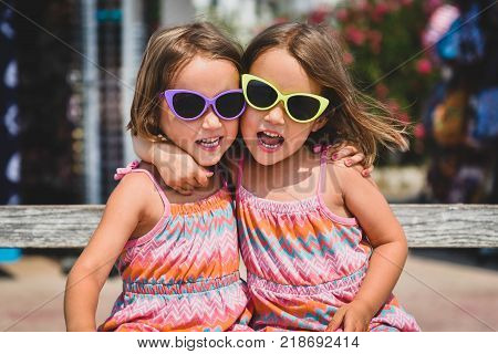 Identical Twin Girls On Summer Vacation Posing For Camera.