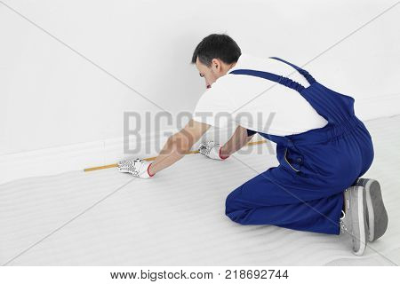 Worker with tape measure preparing to install new carpet flooring