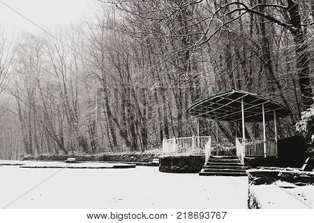 Empty snow-covered arbour in an empty Park
