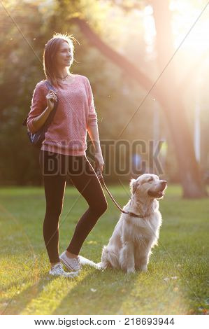 Image of beautiful woman on walk with dog in summer park on lawn. Lensflare effect