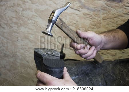 Shoe repair. Shoemaker is repairing shoe. Hands taken closeup. Concept of man job. shoemaker holding hammer.