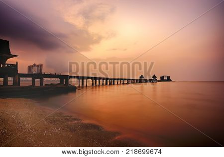 Old bridge in the sea on twilight time after sunsetnature of outdoor tropical coast in Thailand of Popular attractions the name is Wat Jit-ta-pha-wan in Chonburi province.