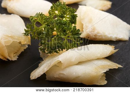 smoked and sliced north atlantic wild halibut with parsley on slate