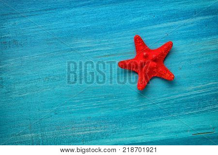 Summer board of red star fish on blue wooden background for holiday concept