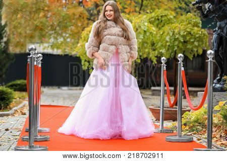 Beautiful young woman in white dress and fur coat on red carpet, outdoors
