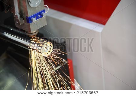 The laser cutting machine cutting the stainless tube.Tha sparking light from laser cutting machine.