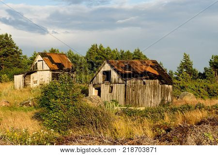Abandoned houses in the Baltic Sea. Shore, nature and ruins facilities architecture concept. Mohni, small island in Estonia, Europe. poster