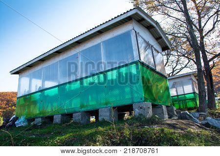 Long pavilion based on cement blocks. White-green gazebo.