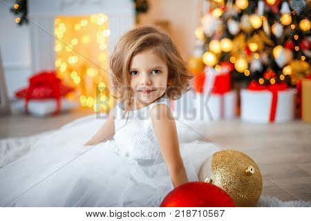Cute little girl in white tender beautiful dress sitiing in brightly decorated room full of Christmas decoration.
