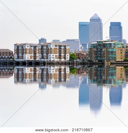 Skyscrapers in Canary Wharf a major financial district in London and their reflections from Thames river