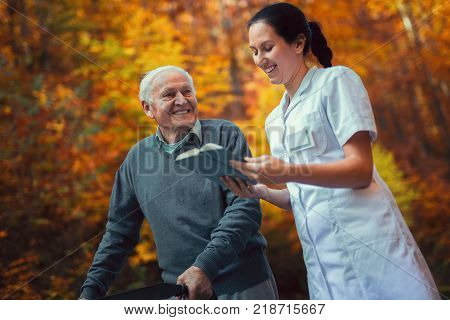 Smiling nurse reading book to senior man that uses walker with caregiver outdoor