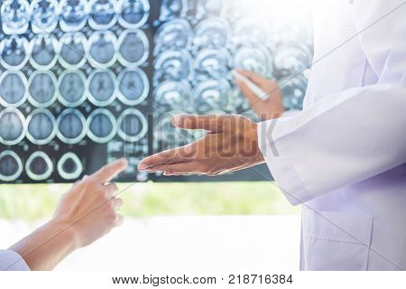 Two Doctors Analyzing A Scan Or X-ray Film Or  Explains A Ct Scan Together With Serious Thoughtful E