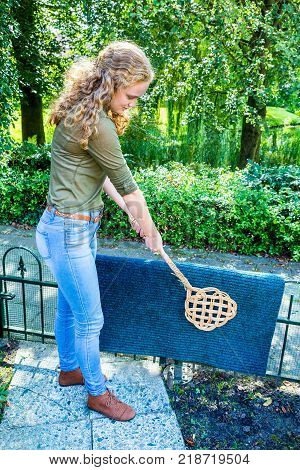 Young caucasian woman beating door mat with carpet beater outside