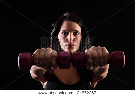 Young Woman Using Hand Weights For Power Workout