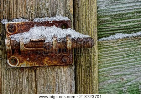 rusty iron latch under the snow on a wooden door