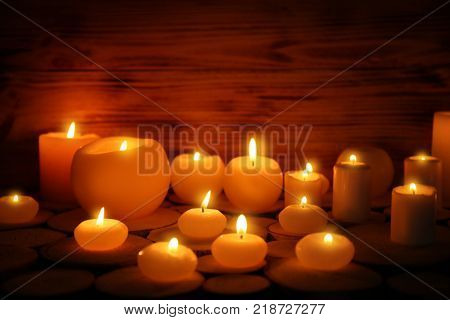 Many burning candles on wooden background