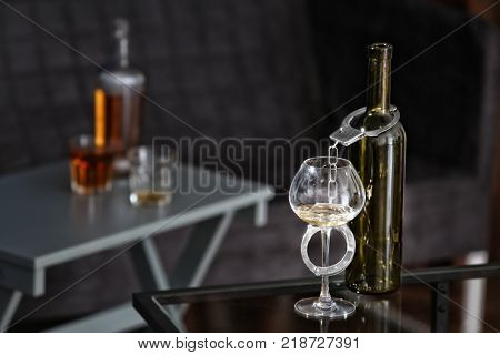 Bottle and glass with handcuffs on table. Alcohol dependence concept