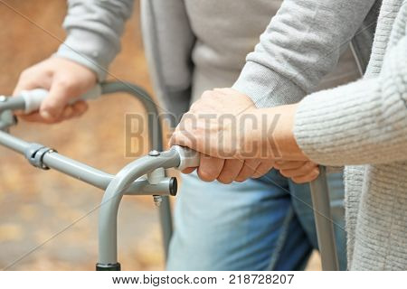 Elderly woman and her husband with walking frame outdoors, closeup