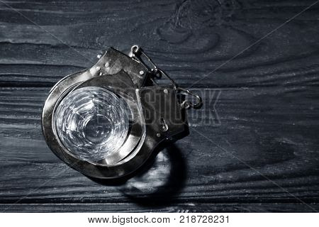 Glass and handcuffs on dark wooden background. Alcohol dependence concept