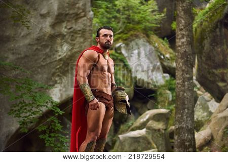 Portrait of a handsome Spartan warrior with strong muscular body wearing red cloak standing in the woods looking away thoughtfully copyspace nature confidence masculinity gym power strength.