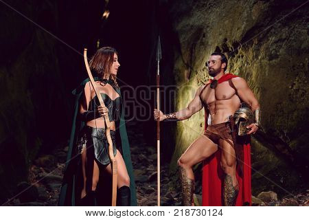 Shot of a medieval couple Spartan warrior and his woman standing in the woods with their weapons family love romance relationships people historic characters bravery courage emotions affection.