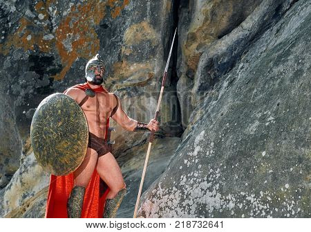 Shot of a brave muscular Spartan warrior with a shield and a spear standing on top of a rock looking around copyspace war fighting armed armor protection safety guard guardian abs.