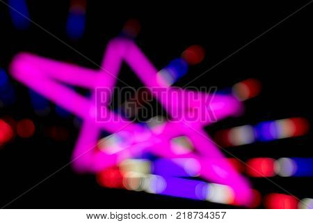 Abstract pink color of glow fluorescent on black background in star shape