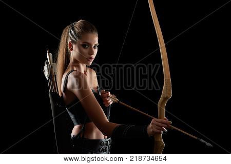 Studio portrait of a gorgeous young long haired female warrior looking to the camera holding a bow posing on black background copyspace archer archery medieval character Amazon tribe.