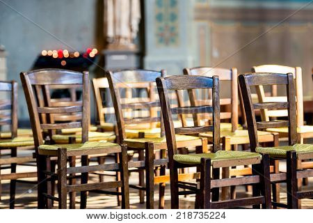 A close up view of wooden chairs with green wicker seats lined up in front of a rack holding lit votive candles. The background shows a nice bokeh of the candles.