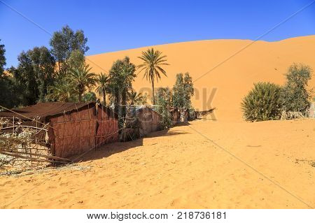 Camp in the Sahara Desert at Merzouga Morocco in North Africa. A brilliant sun shines down from a clear blue sky on a bivouac.