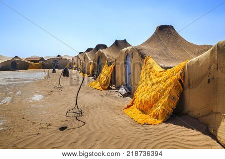 Nomadic settlement in the Sahara Desert .The structures all have blue doors and are made from woven cloth.