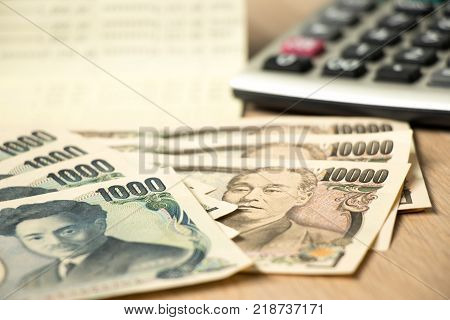 Japanese yen banknote bank statement book and calculator on wood table background