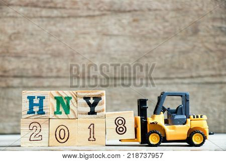Toy yellow forklift hold letter block 8 to complete word HNY 2018 (Abbreviation of Happy new year) on wood background
