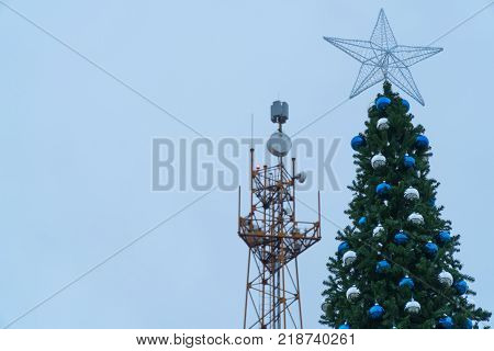 Main tree of the city on the background the tower of the base station communications. During the Christmas holidays people often communicate via phone and Internet communications.