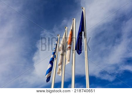 Cyprus, Greece, Eu And Larnaka Municipality Flags On Poles. Cloudy Sky Background.