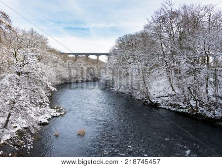 Snow covered trees frame the old Pontcysyllte Aqueduct near Chirk carrying Llangollen Canal across river Dee