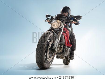 Biker in black jacket and helmet sitting on his sportive bike on blue studio background