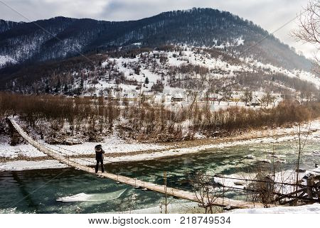 cold flow of river in snowy mountains. ice and snow on the rocky shore. gorgeous winter scenery in rural area on a cloudy day.