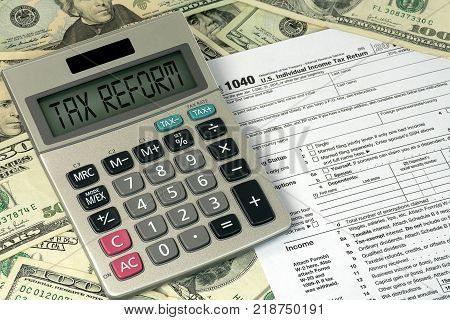 tax reform text sign on calculator with 1040 income tax form and American paper money