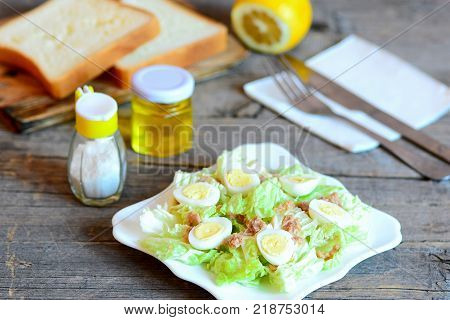 Tuna and chinese cabbage salad. Salad with chinese cabbage, quail eggs and canned tuna fish on a served plate. Fork, knife, lemon, bread pieces on an old wooden table. Cabbage and tuna fish recipe